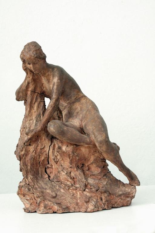 Postać kobiety siedzącej na skale